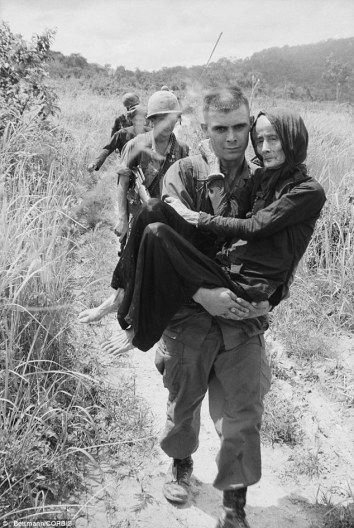 Soldier in Vietnam carries an elderly woman to safety.