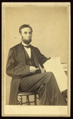 Seated pose of Republican President Abraham Lincoln holding Emancipation Proclamation papers. 1863.