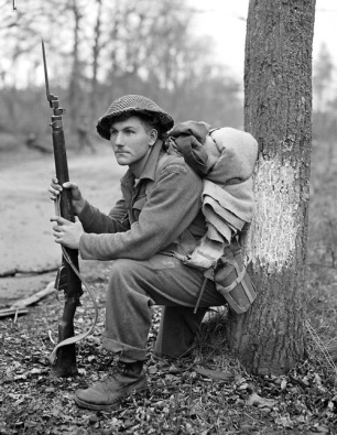 Private K.O. Earl, of the Perth Regiment, stops for a rest in the forest north of Arnhem, as the 5 Canadian Division advances. 15 Apr 1945, Arnhem (vic), The Netherlands.