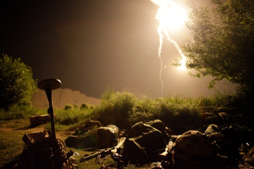 Canadian soldiers sleep as a flare burns over them during a special operation at Sanjaray in Kandahar Province