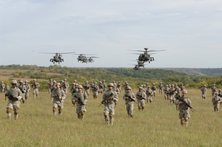 soldiers-crossing-field-with-helicopters-overhead-e1399099919624