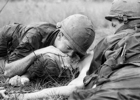 Medic James E. Callahan of Pittsfield, Mass., gives mouth-to-mouth resuscitation to a dying soldier in war zone D, about 50 miles northeast of Saigon, June 17, 1967. Thirty-one men of the 1st Infantry Division were reported killed in the guerrilla ambush, with more than 100 wounded. (AP Photo/Henri Huet)