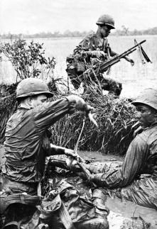 Vietnam War - 1st Infantry Division Medic treating a wounded soldier.
