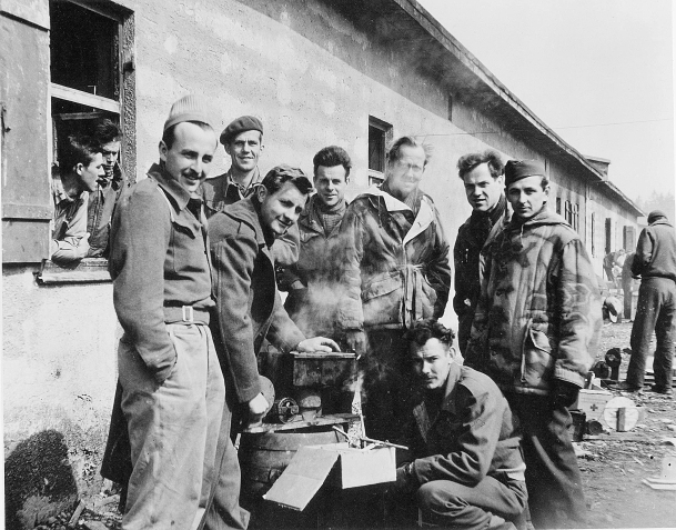 """Charles Woehrle is included in a group photo taken at at Stalag VII A Moosburg, Germany. Pictured are (L-R) John Fitzpatrick (hand in pocket), Ed Stephenson (beret), Ernie Sands (bending over stove), Francis """"Fran"""" Finnegan, John Lindquist,Woehrle, Jim Houser and Lt. Marshall Draper (kneeling) of the 15th Bombardment Squadron. Draper had the unfortunate distinction to be the first U.S. POW in Germany, shot down on 21 June 1942. Lindquist and Houser are wearing German reversible padded parkas, probably gathered as """"war booty"""". These men were roommates at Stalag Luft III, South Compound, Block 130, Room 10. They kept together on the march in January 1945, sharing food and emotional support. (Photo courtesy of Ben van Drogenbroek through the 458th Bombardment Group (H)"""