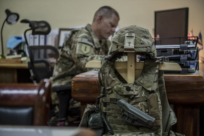 A U.S. Navy Commander works on mission planning in his office at Salerno. Due to the constant threat of incoming rounds, the Commander's armor is stored within reach.