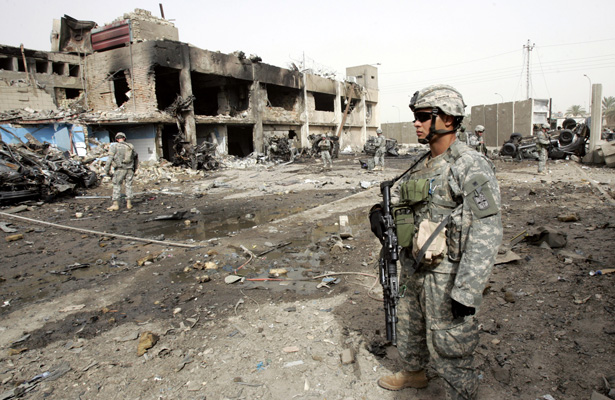 U.S. soldiers inspect the scene of a car bomb attack outside the office of the state-run newspaper in Baghdad on August 27, 2006. (Ali Jasim/Reuters)