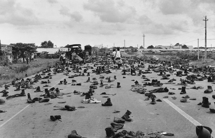 "April 30, 1975 Combat boots litter the road on the outskirts of Saigon, abandoned by ARVN soldiers who shed their uniforms to hide their status. ""I'll never forget the shoes and the loud 'thump, thump, thump' sound as we drove over them,"" recalled the photographer. ""Decades of war were over and we finally had peace."""