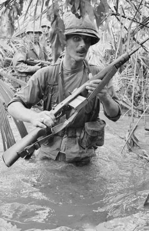 U. S. First Division soldiers are waist deep as they ford a stream near Bien Hoa, South Vietnam, in search of Viet Cong, Aug. 7, 1965. The division has been seeking the communist guerrillas around their positions since the American arrival in Vietnam in July. (AP Photo/Horst Faas)